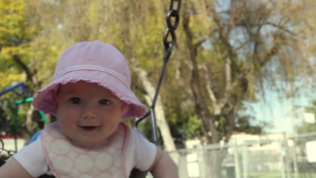 cu baby sitting on swing at park, mother pushing / los angeles, california, usa - 男の赤ちゃん一人点の映像素材/bロール