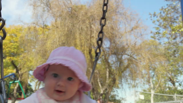 cu baby sitting on swing at park, smiling / los angeles, california, usa - 男の赤ちゃん一人点の映像素材/bロール