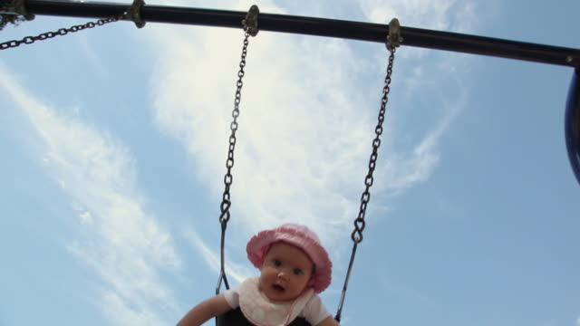 ms baby sitting on swing at park, smiling / los angeles, california, usa - 男の赤ちゃん一人点の映像素材/bロール