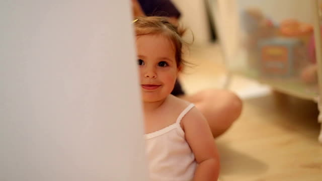 vídeos de stock, filmes e b-roll de bebê sentado no chão e brincando de esconde e esconde, peek a boo - escondendo