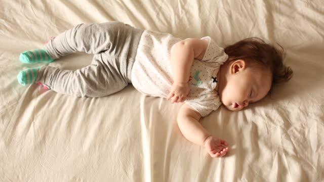 vídeos de stock, filmes e b-roll de a baby sleeping indoors on a white sheet. - vida de bebê