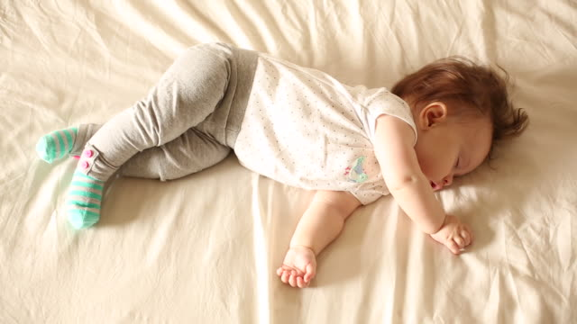 A baby sleeping indoors on a white sheet.
