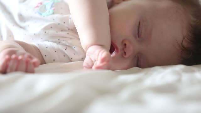 a baby sleeping indoors on a white sheet. - abbigliamento da neonato video stock e b–roll