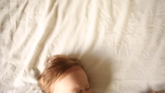 a baby sleeping on a bed in her pajamas inside of a home. - one baby girl only stock videos & royalty-free footage