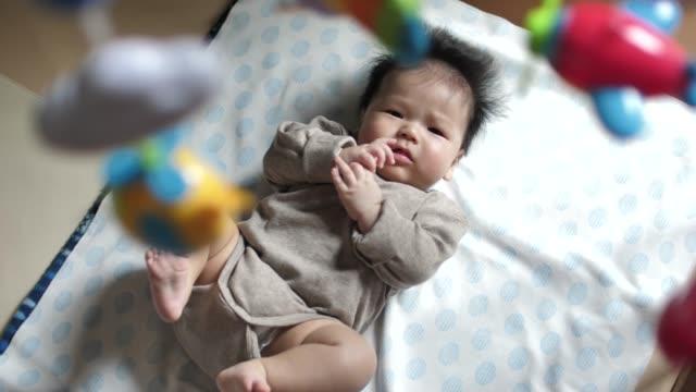 携帯電話をぶら下げで眠っている赤ちゃん - 赤ちゃんのみ点の映像素材/bロール