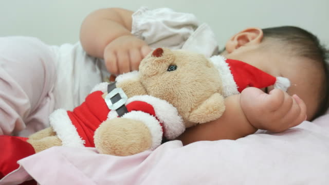 baby sleeping with hold santa doll - doll stock videos and b-roll footage