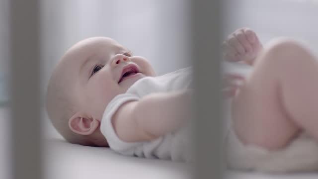 baby smiles in crib - camera dei bambini video stock e b–roll
