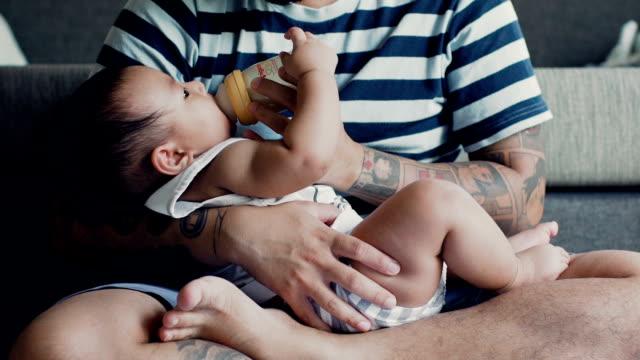 vídeos de stock, filmes e b-roll de querida, aconchegando-se nos braços do seu pai durante a mamada - alimentando