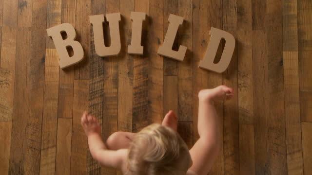 """baby er definiert """"bauen"""" - ein männliches baby allein stock-videos und b-roll-filmmaterial"""