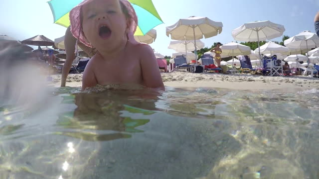 baby splashes the water in the sea, sitting and playing - nappy stock videos and b-roll footage