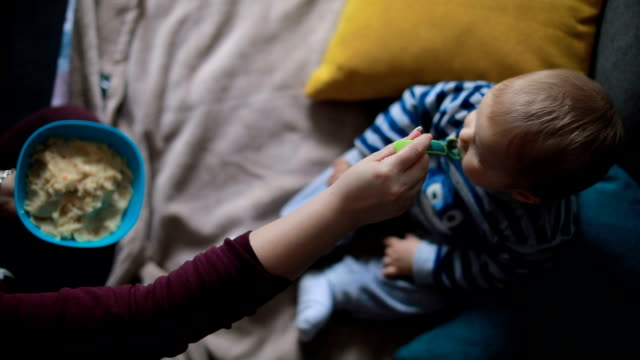 デジタル タブレットの母は彼をフィード中に赤ちゃんの視線 - 見つめる点の映像素材/bロール