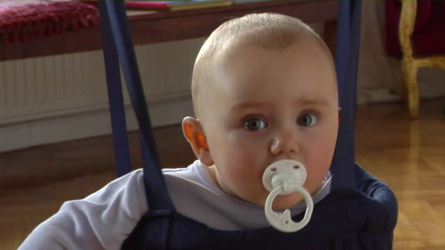 cu baby (8-9 months) sucking on pacifier while sitting in baby bouncer / berlin, germany - pacifier stock videos and b-roll footage