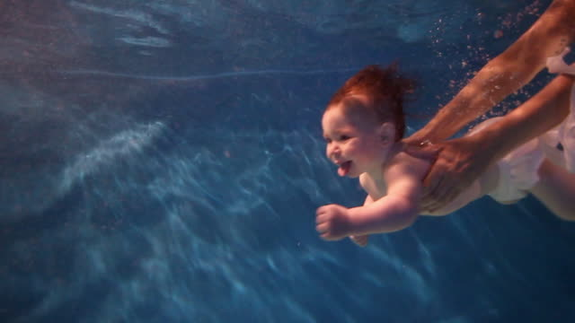 SLO MO WS baby swimming underwater