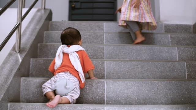 赤ちゃんの幼児 '第一歩' の家の階段を登る - 階段点の映像素材/bロール
