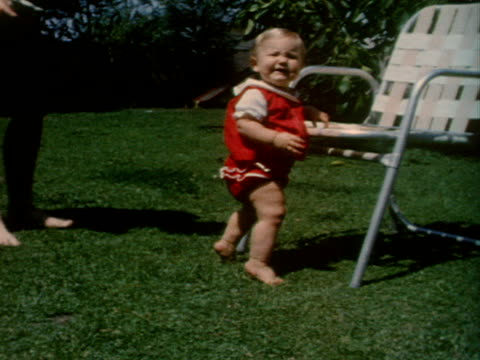 A baby uses a lawn chair to help her stand.