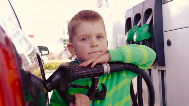 baby using a gasoline pump at the gas station - gasoline stock videos & royalty-free footage