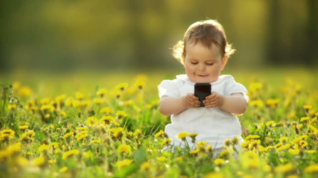 hd slow-motion: baby using mobile phone outdoors - one baby girl only stock videos & royalty-free footage