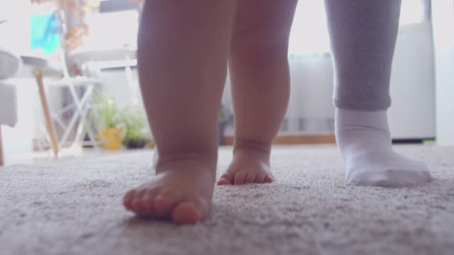 baby walking supported by his mother - gradino video stock e b–roll