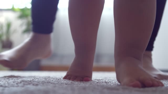 baby walking supported by his mother - flooring stock videos & royalty-free footage