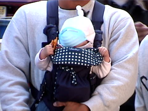 a baby wears a dust mask at ground zero in the aftermath of the 9/11 terrorist attacks in downtown manhattan - pollution mask stock videos & royalty-free footage