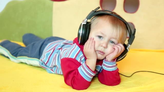 vídeos y material grabado en eventos de stock de bebé con auriculares - mano en la barbilla