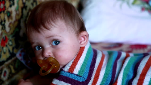 baby with pacifier lying on the front and looking at camera - lying on front stock videos & royalty-free footage