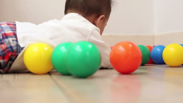 a baby's close-up,trying to grasp color balls in a room - ボール点の映像素材/bロール