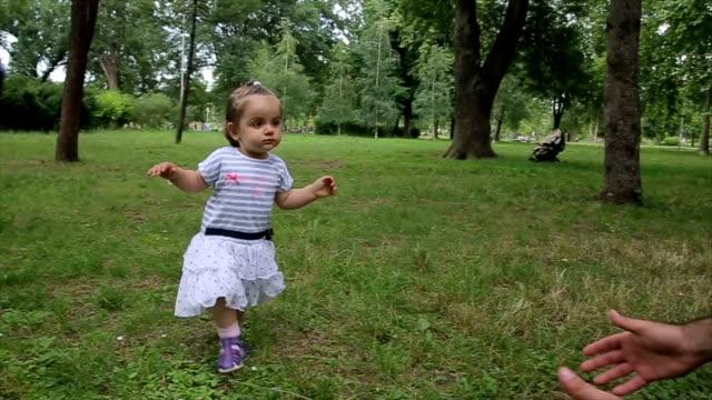 babys erste schritte auf dem rasen. die ersten eigenständigen schritte. - erste schritte stock-videos und b-roll-filmmaterial