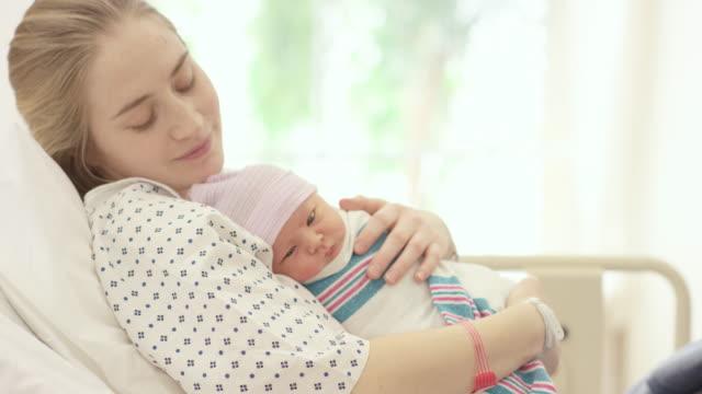 vídeos de stock, filmes e b-roll de primeiro swaddle do bebê - agarrar