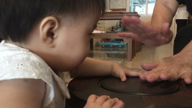 赤ちゃんの手と母親が一緒に遊んで - ドラム容器点の映像素材/bロール