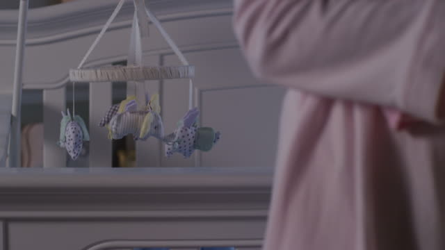 A baby's mobile hangs over the crib as parents wearing pajamas eclipse camera as they walk around in nursery.