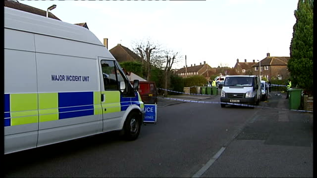 babysitter found murdered in borehamwood; england: hertfordshire: borehamwood: ext general views police officers by cordon tape outside house... - ボーハムウッド点の映像素材/bロール