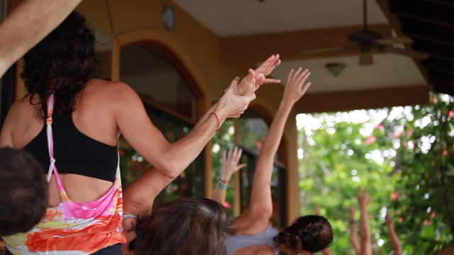 back angle shot of a yoga teacher/woman correcting the posture of a yoga student and outdoor yoga deck surrounded by lush colourful vegetation and female yoga students - kelly mason videos stock videos & royalty-free footage
