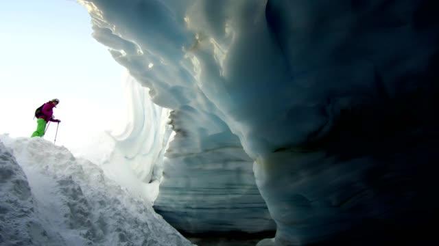 backcountry skifahrer eine gletschereis höhle erkunden - land stock-videos und b-roll-filmmaterial