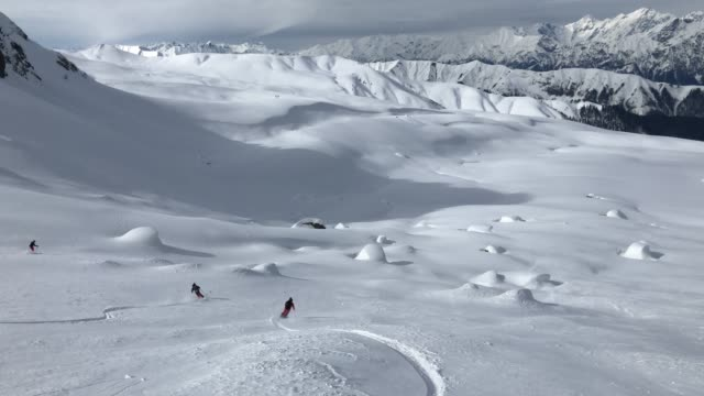 vídeos de stock e filmes b-roll de back country skiers descending mountain, deep powder snow - casaco de esqui
