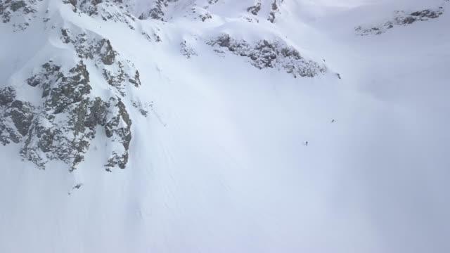 Esquiadores de parte país descendiendo la montaña, nieve polvo profunda