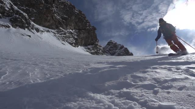 back country skiers descending mountain, deep powder snow - ski jacket stock videos & royalty-free footage
