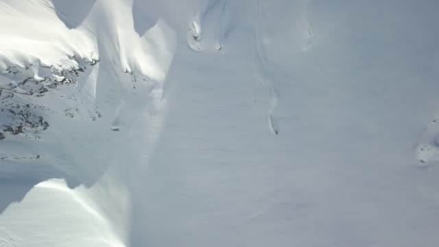 back country skiers descending mountain, deep powder snow - skiing and snowboarding stock videos and b-roll footage
