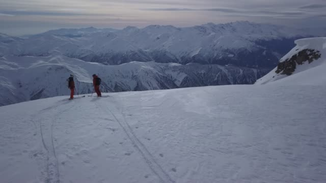 back country skiers standing on mountain top - ski jacket stock videos and b-roll footage