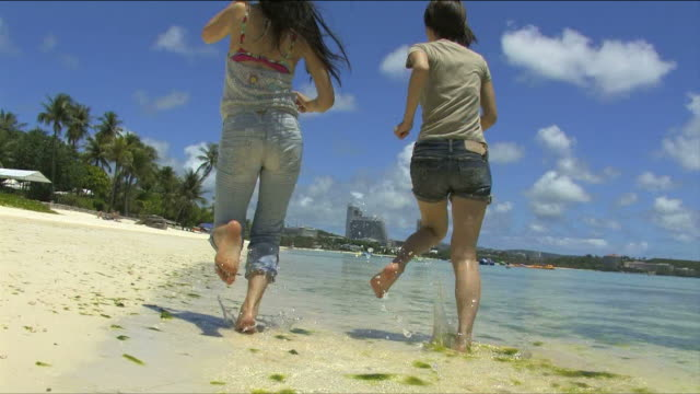 back figure of two young women who are running on the beach   - guam stock videos and b-roll footage