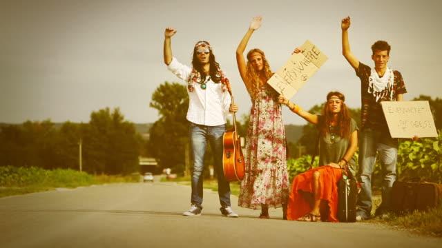vídeos de stock, filmes e b-roll de nos anos 70: hippies na estrada pedindo carona - chama