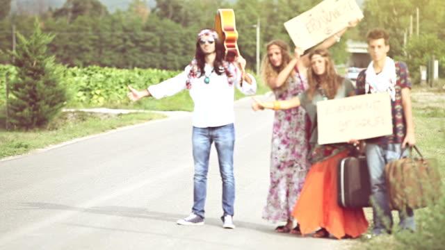vídeos de stock, filmes e b-roll de nos anos 70: hippies na estrada pedindo carona - hippie