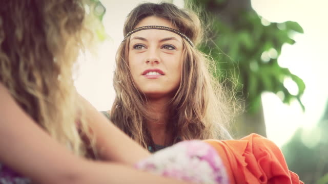 stockvideo's en b-roll-footage met back in the 70s: two hippie women talking - haarband