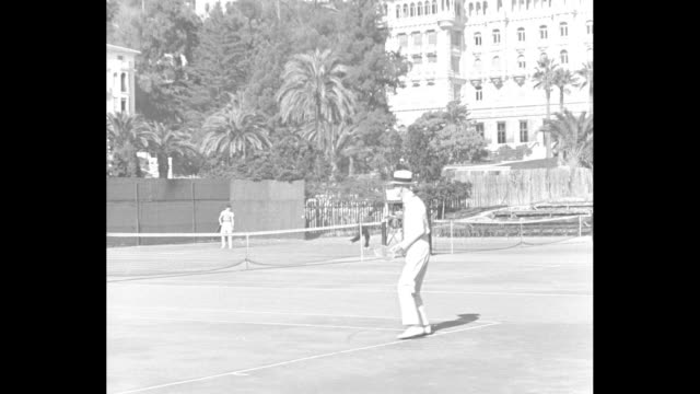 CU back left side of King Gustaf V of SwedenÕs head wearing panama hat serving tennis ball / VS Gustaf in cardigan playing in coed doubles math / MS...