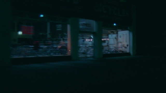 vidéos et rushes de 3/4 back left travelling past dark stores, gas stations and several used car lots (long beach) - night - image animée