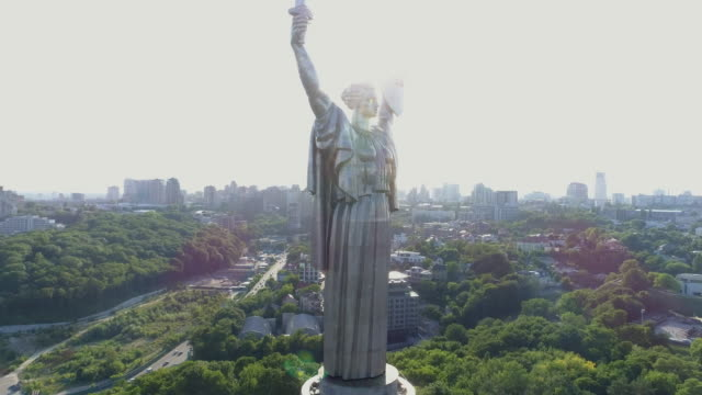 back lit panoramic aerial view of motherland monument in kiev - ウクライナ点の映像素材/bロール