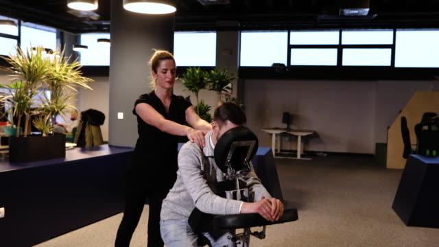 vídeos de stock e filmes b-roll de back massage on a mobile massage chair - dor no pescoço