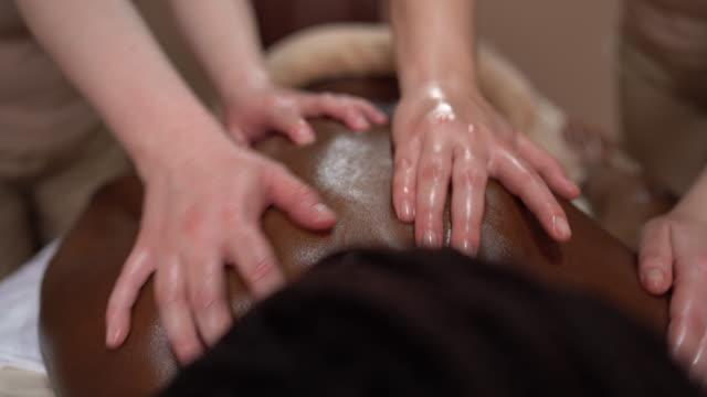 vidéos et rushes de traitement de massage du dos - stock vidéo - banc de massage