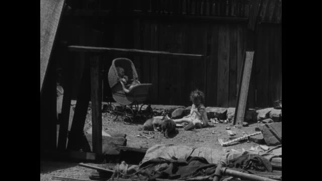 vidéos et rushes de back of apartment building w/ laundry hanging on lines near fire escapes housing near factory child playing in vacant lot low income housing near... - 1936
