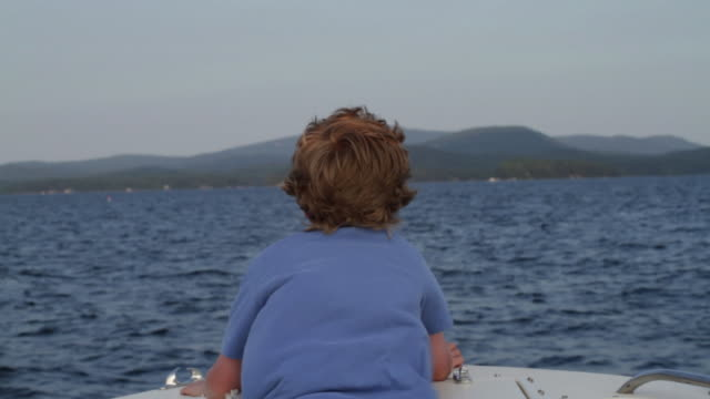 ms back of boy looking out from boat / wolfebro, nh, usa      - nautical vessel stock videos & royalty-free footage